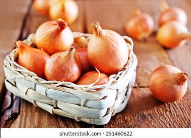 raw onion in basket and on a table
