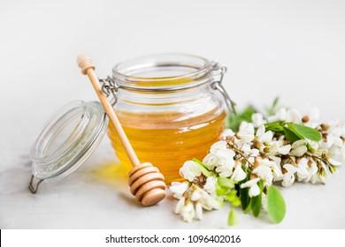 Raw organic acacia flowers honey jar with dipper and acacia flowers