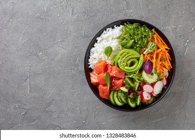 Raw Organic Ahi salmon Poke Bowl with rice, seaweed, avocado rose, radish, carrot, cucumber and green salad, sprinkled with spring onion and sesame seeds, view from above, flatlay