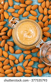 Raw Organic Almond Butter with a few peeled almond on a quartz stone Background. Vertical photo of homemade natural almond butter in a glass jar. Pastel colors. View from above.