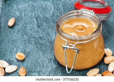 Raw Organic Almond Butter with a few peeled almond on a quartz stone Background.