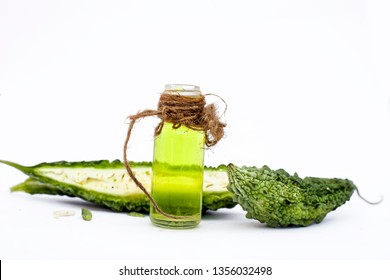 Raw organic bitter melon or Bitter Cucumber or Bitter Gourd isolated on white along with its detoxifying essential oil in a transparent glass bottle.