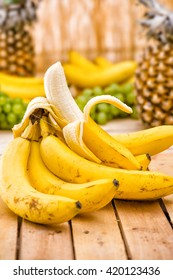 Raw Organic Bunch of Bananas Ready to Eat. Ripe yellow peeled bananas with oder fresh fruits, pineapple, grapes on wooden background, view from above, bananas in a wooden box, food, meal, vitamins,