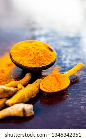 Raw organic famous and essential spice i.e. Turmeric or haldi or Curcuma or Curcuma, saffron des Indes in a clay bowl along with its powder on brown colored wooden surface.