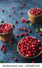 Raw organic fresh cowberry or lingonberry in wooden bowls on dark stone table, healthy lifestyle concept