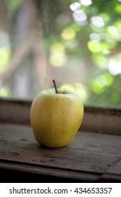 Raw organic Golden apple on a wooden table by the window