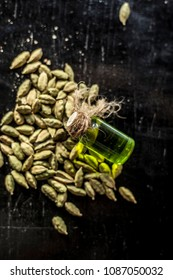 Raw organic green cardamom or elaichi or Elettaria cardamomum or true cardamom with its essence on wooden surface used in many beverages as a flavoring liquid.;