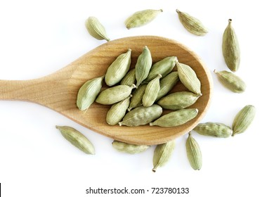 Raw organic green cardamom pods in wooden spoon isolated on white background. Top view