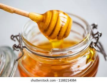 Raw organic honey in a jar with dipper closeup, healthy natural sweetener