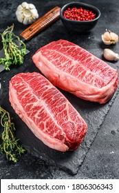 Raw organic meat Twagyu oyster top blade steak. Black background. Top view
