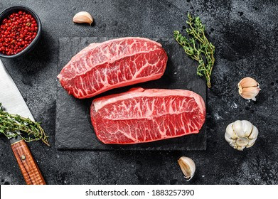 Raw organic meat Twagyu oyster top blade steak. Black background. Top view