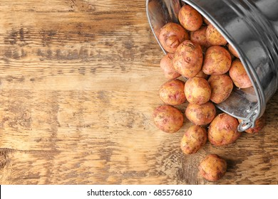Raw organic potato with bucket on wooden table