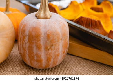 Raw organic pumpkin, butternut, squash, and roasted pumpkin slices close up on kitchen table