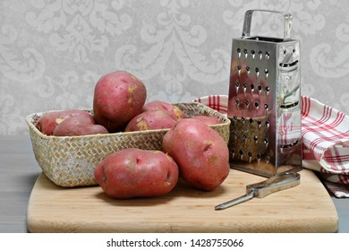 Raw organic red potatoes in a basket.  Basket is on cutting board with peeler and shredder.