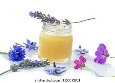 Raw organic royal jelly on white board surrounded by flowers on white