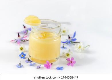 Roher organischer Gelee des Königs in einer kleinen Flasche mit einem kleinen Löffel auf einer kleinen Flasche auf weiß