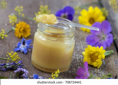 raw organic royal jelly in a small bottle with litte spoon on small bottle surrounded by flowers wooden background
