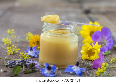 raw organic royal jelly in a small bottle with litte spoon on small bottle surrounded by flowers on old wooden background