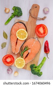 Raw organic salmon steak with vegetables and spices on a wooden background. Selective focus.