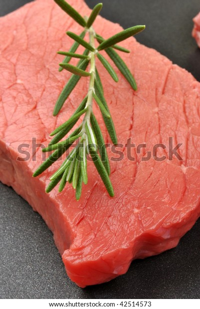 raw organic steak with rosemary in a pan