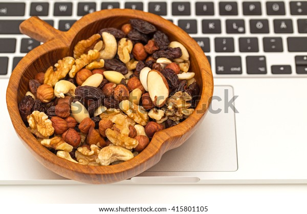 Raw organic trail mix from cashew nuts, raisins, walnuts, macadamia, hazelnuts, brazil nuts, almonds in apple olive wooden bowl on laptop keyboard background, close up