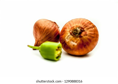Raw organic two vegetables isolated on white which are onion or pyaaj or pyaaz along with cut chili or hari mirchi or lili mirchi.