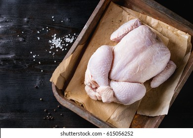 Raw organic uncooked whole chicken with salt and pepper on backing paper in old oven tray over black burnt wooden background. Top view with space.