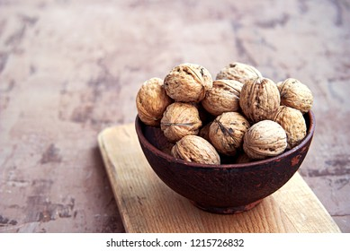 Raw organic walnuts in the shell in a brown clay bowl. Harvest nuts.