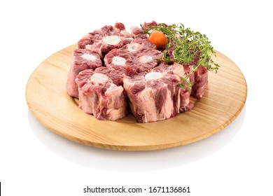 Raw oxtail, the culinary name for the tail of cattle, ready to be cooked. On a cutting board, isolated on white background.