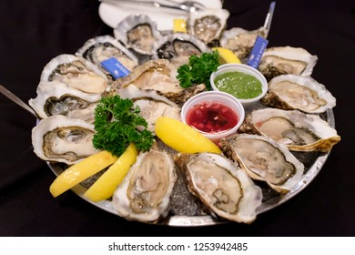 raw oysters serve on an ice plate with lemon and sauce