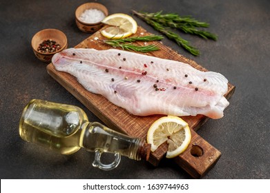 raw pangasius fillet on a cutting board with lemon, oil and spices on a stone background. raw fish.
