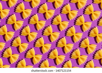 Raw pasta farfalle close-up on purple background. Poster or background.