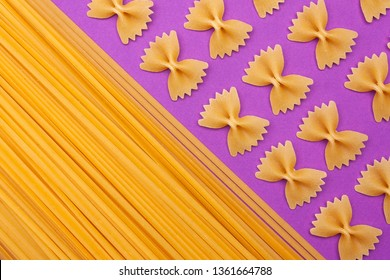 Raw pasta farfalle and spaghetti on purple background with copyspace.
