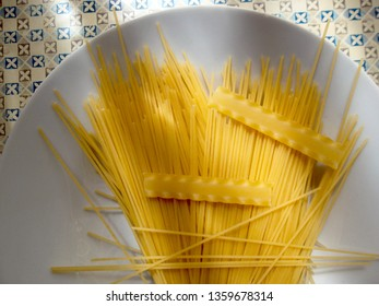 RAW PASTA ON A WHITE DISH ILLUMINATED BY THE MORNING SUN THROUGH THE WINDOW CURTAINS WITH SHADOWS