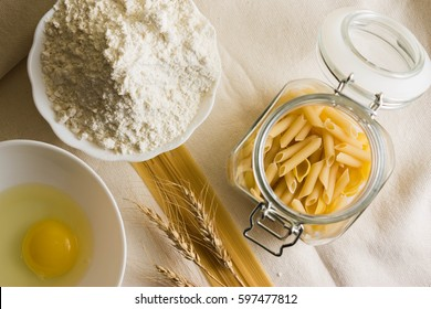 Raw pasta on a white sacking and ingredients. Different types of pasta.