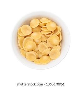 Raw pasta orecchiette in white small bowl. Isolated