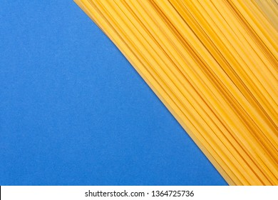Raw pasta spaghetti on blue background with space for text.