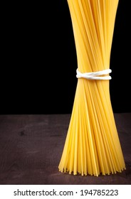 raw pasta spaghetti on wood table with space for text, typical italian cuisine