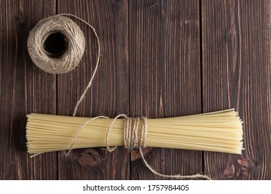 Raw pasta spaghetti with packthread and copy space on wooden background. Top view of Italian cuisine ingredient.