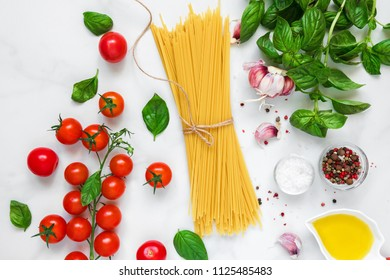 raw pasta spaghetti with tomatoes, garlic and basil on white marble background. cooking concept. top view. flat lay