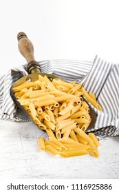 Raw pasta type penne rigate in copper bailer, on white background.