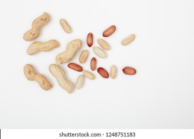 Raw peanuts , shelled, husk, whole, halves , Pattern of nuts form. isolated on white background, top view