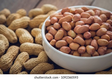 Raw peanuts in white bowl and peanut shell on wooden table