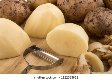 raw peeled organic potatoes on a wooden board