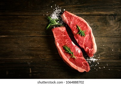 raw Picanha steak on wooden background in rustic style with salt and herbs