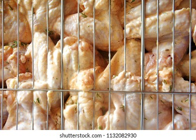 raw pickled chicken wings are cooked for frying on the fire greens are anointed