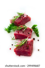 Raw pieces of beef with spices over white