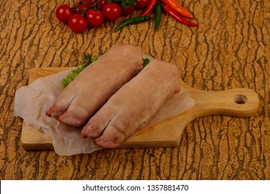 Raw pig's hoof ower wooden background