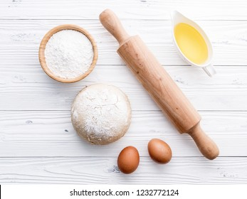 Raw pizza dough and rolling pin on wooden background