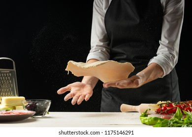 Raw pizza ingredients on a wooden table, the chef prepares pizza on a dark background